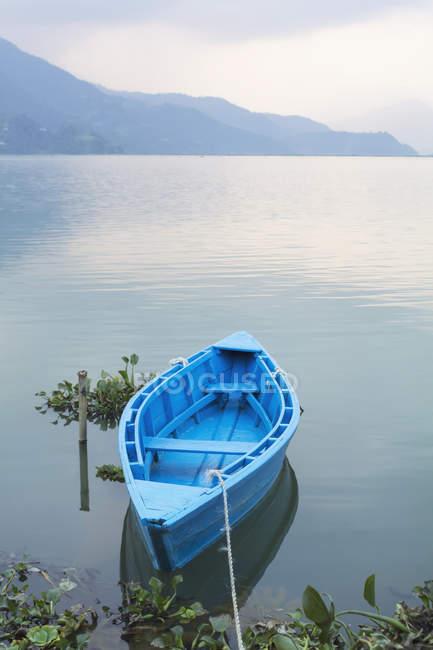 Голубая парусная лодка на якоре в озере с силуэтом горы на заднем плане. Непал, Западный регион, Зона федаки, Покхара, Мансавар, озеро Пхева — стоковое фото