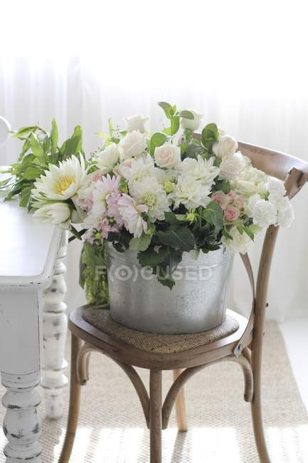 Bucket of beautiful delicate flowers on chair indoors — Stock Photo