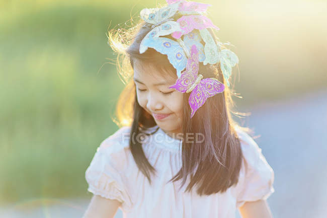 Smiling girl with butterflies in hair looking down outdoors — Stock Photo