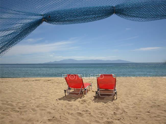 Grèce, Thassos, Chaises longues rouges sur la plage — Photo de stock
