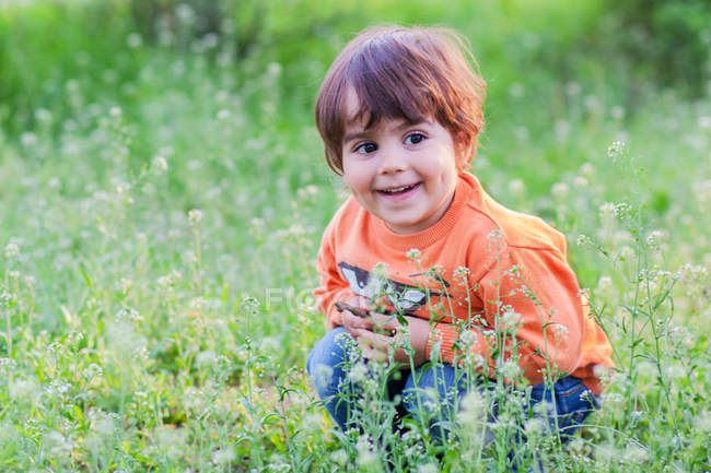 Smiling little Boy sitting in grass — Stock Photo