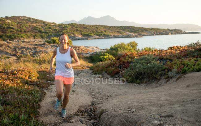 Франция, Корсика, улыбающаяся женщина, бегущая по берегу — стоковое фото