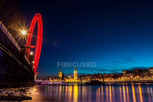 London Eye in motion and illuminated cityscape reflecting in river, London, UK — Stock Photo