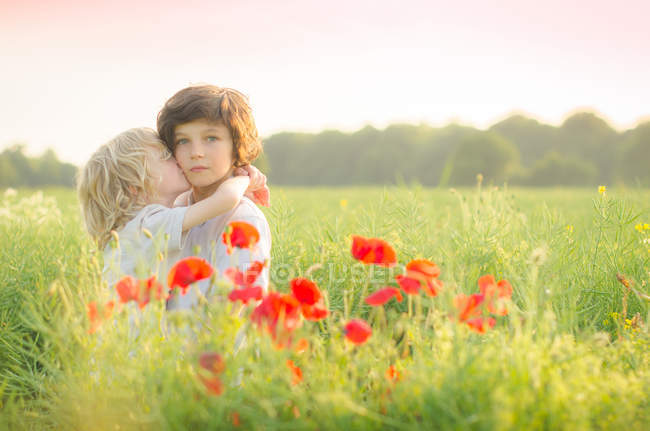 Two caucasian brothers hugging and kissing in field — Stock Photo
