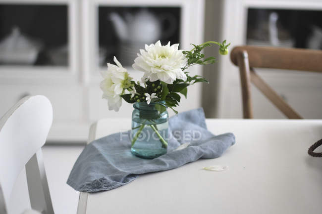 Jar of cut flowers on dining table — Stock Photo