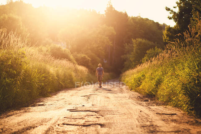 Man walking on rural path in countryside at sunlight — Stock Photo