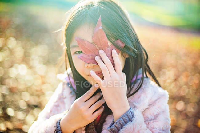 Menina, escondendo o rosto por trás de uma folha na natureza — Fotografia de Stock