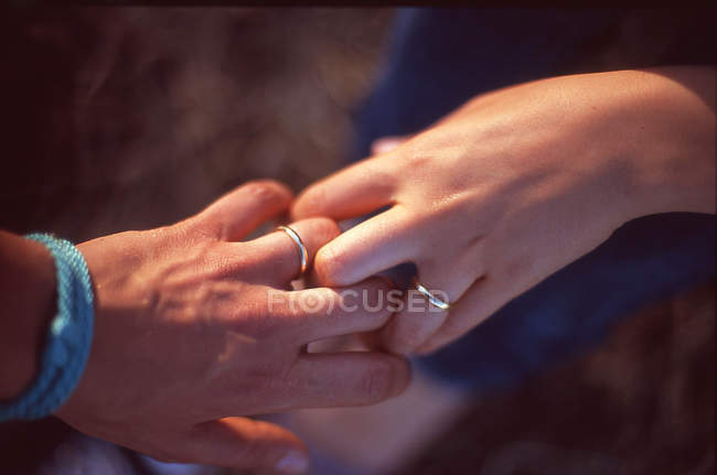 Cropped image of couple with wedding rings holding hands against blurred background — Stock Photo
