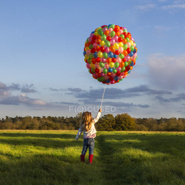 Girl walking with colorful balloons in meadow — Stock Photo