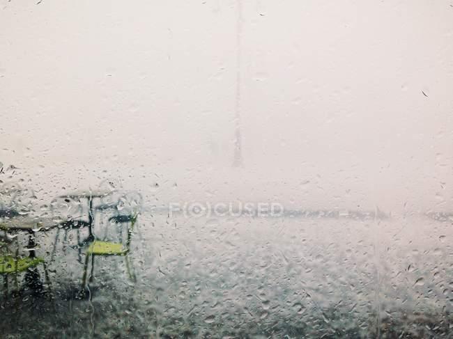 Vista a través de un vaso de sillas y mesas mojadas bajo la lluvia - foto de stock