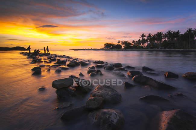Indonesia, Sumatera, West Sumatra, Silhouette di persone sulla spiaggia al tramonto — Foto stock