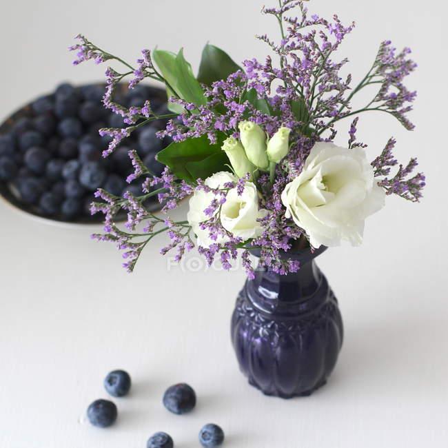 Свіжі Квіти зрізані в Ваза з чорниці, на білій поверхні — стокове фото