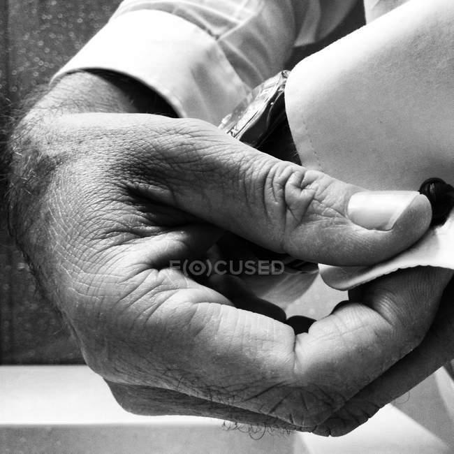 Cropped image de l'homme à mettre sur les boutons de manchettes, monochrome — Photo de stock