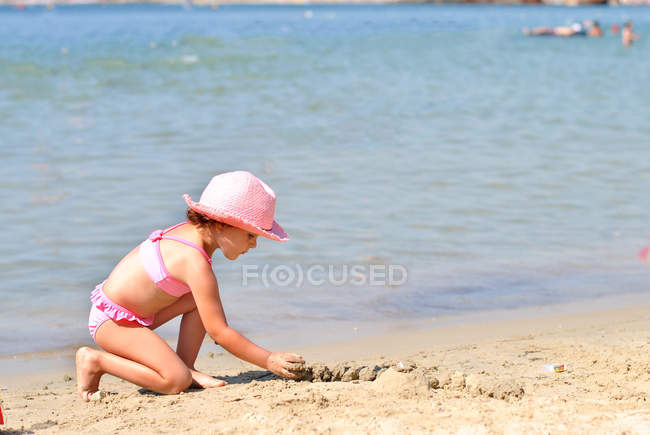 Girl wearing pink hat and swimsuit playing on sandy beach — Stock Photo