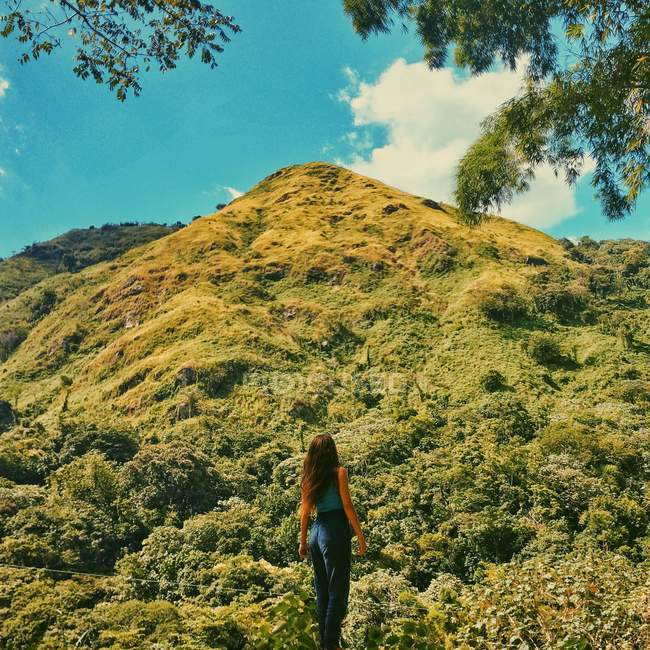 Woman standing in nature and looking at mountain — Stock Photo