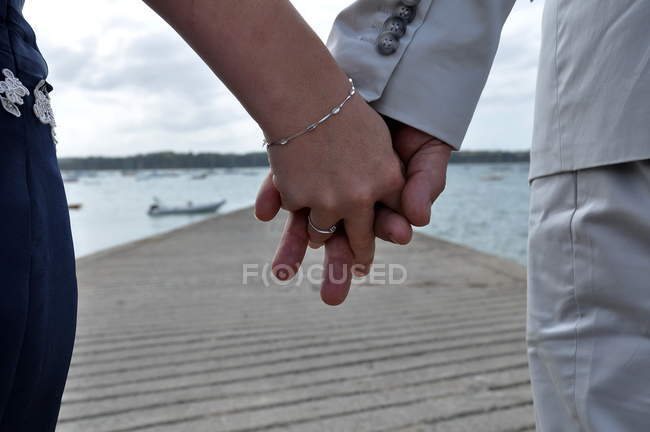 Cropped image of couple holding hands on jetty — Stock Photo