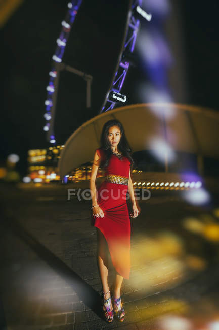 Singapore, Woman wearing red dress standing against glittering lights of Singapore Flyer — Stock Photo