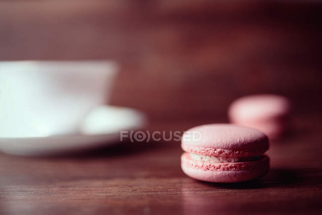 Pink tasty macaroons on wooden table, blurred background — Stock Photo