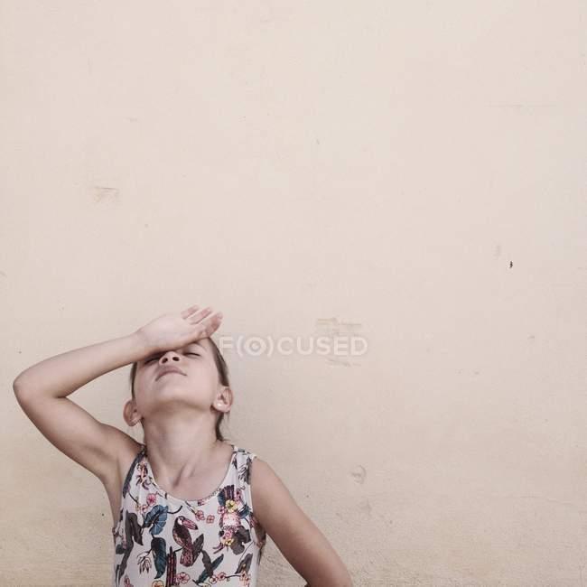 Retrato de menina com a mão na testa contra a parede bege — Fotografia de Stock