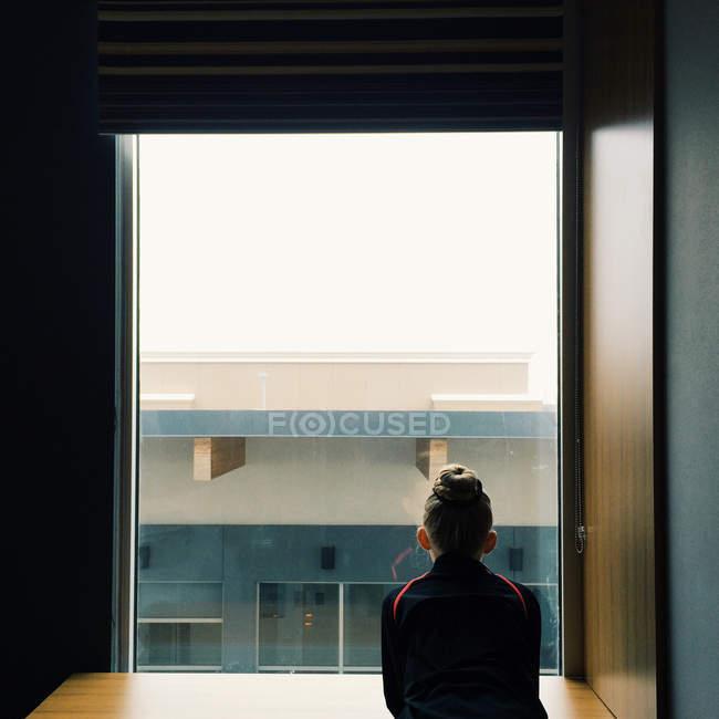 Rückansicht eines kleinen Mädchens, das aus dem Fenster schaut — Stockfoto