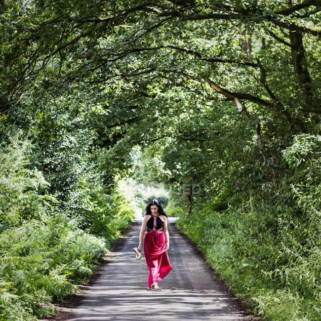 Женщина в длинном платье идет по проселочной дорожке — стоковое фото