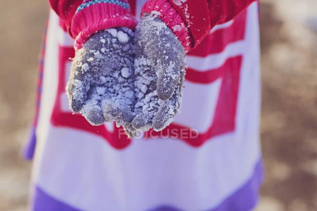 Обрезанное изображение девушки, протягивая заснеженных перчатки — стоковое фото