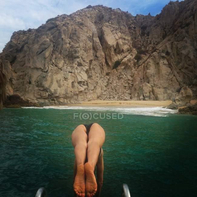 Femme plongeant dans la mer avec falaise sur fond — Photo de stock
