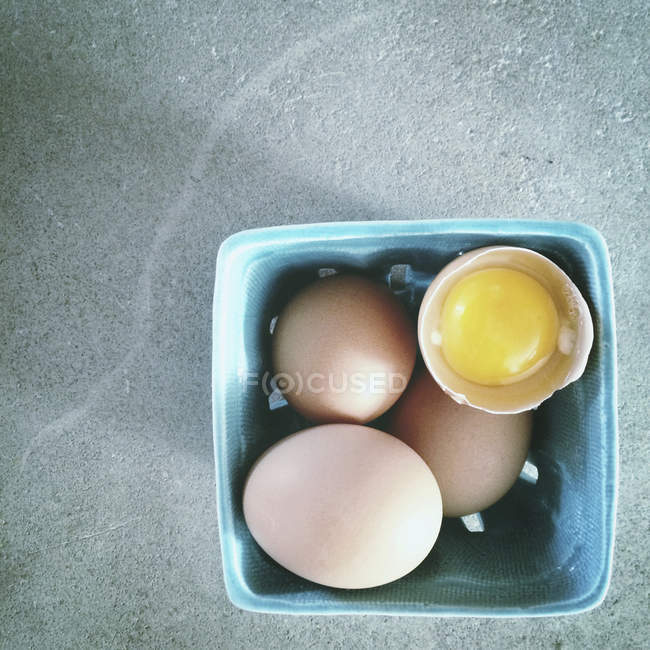 Box of fresh brown eggs with broken one — Stock Photo