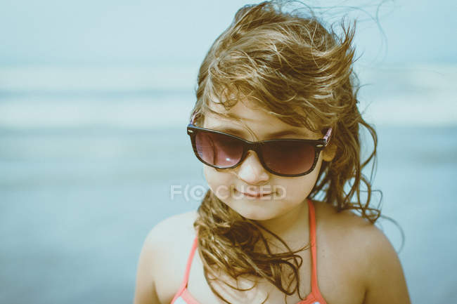 Portrait of girl with windswept blonde hair wearing sunglasses — Stock Photo