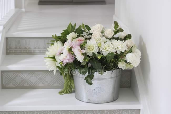 Відро з красивою ніжні квіти зрізані по сходах — стокове фото
