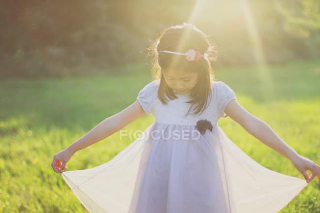 Девушка держит подол платья в солнечном свете на открытом воздухе — стоковое фото