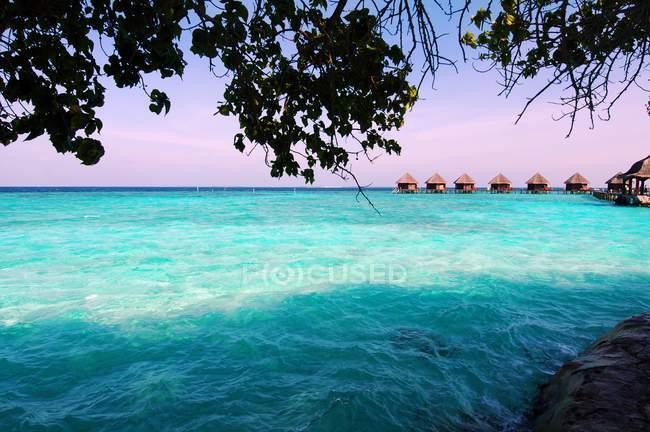 Бирюзовая вода и пляж хижины на горизонте, Мальдивы — стоковое фото