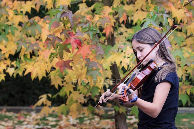 Ragazza che suona il violino con fogliame autunnale sullo sfondo — Foto stock