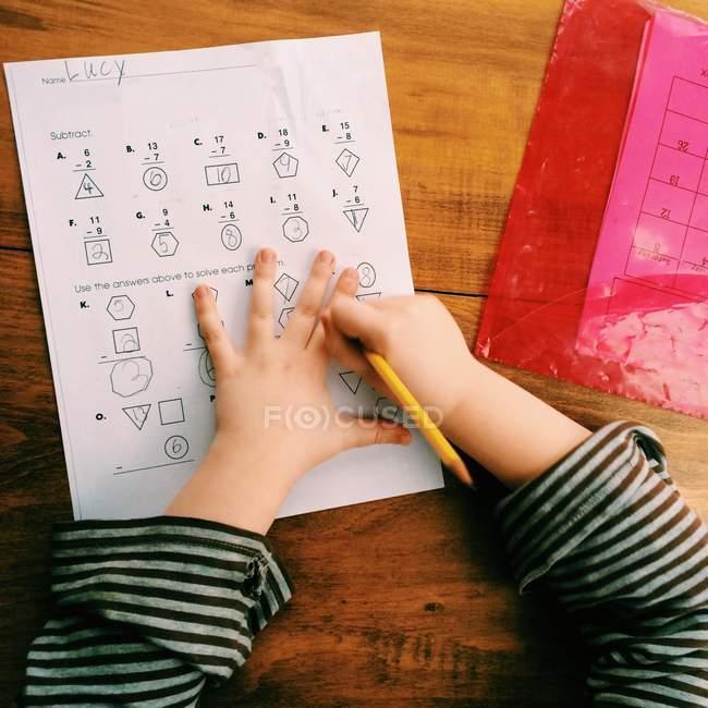 Primo piano vista dall'alto delle mani della bambina che fa i compiti — Foto stock