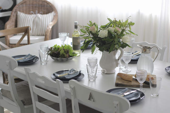Dining table set for lunch with crockery — Stock Photo