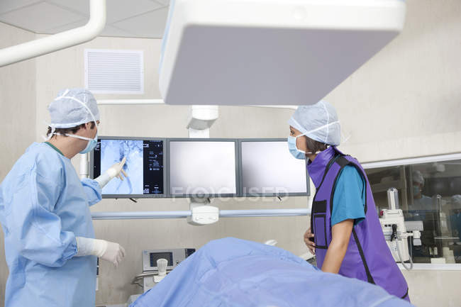 Adult female doctor with patient in room with medical equipment — Stock Photo