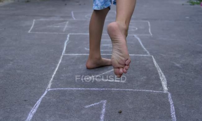 Обрезанное изображение ребенка, играющего в классики на улице — стоковое фото