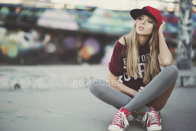 Young confident woman sitting on a skateboard on street — Stock Photo
