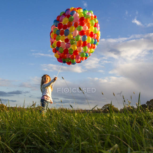Girl standing with colorful balloons in meadow — Stock Photo