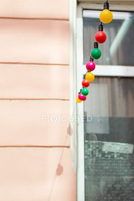 Multicolored fairy lights against window and wall — Stock Photo