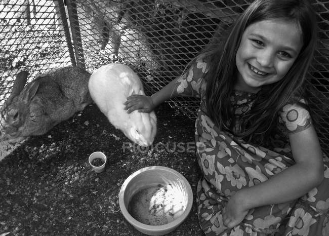 Carino sorridente bambina con coniglio e cavia — Foto stock