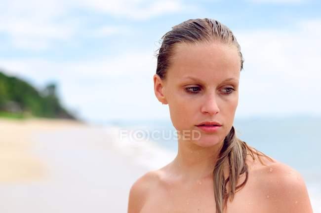 Портрет вдумливі жінки стоять біля пляжу і дивиться вбік — стокове фото