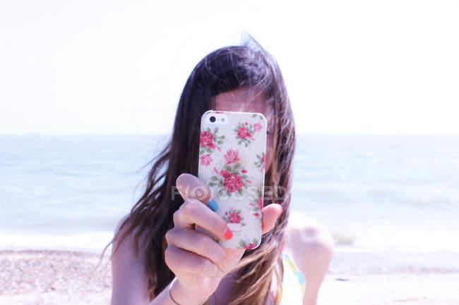 Teenage girl taking photo with smartphone on beach — Stock Photo