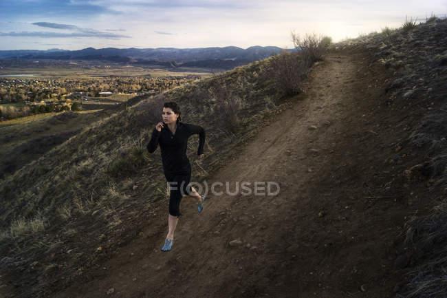США, Colorado, Jeferson County, Golden, Woman running along hillside road — стоковое фото