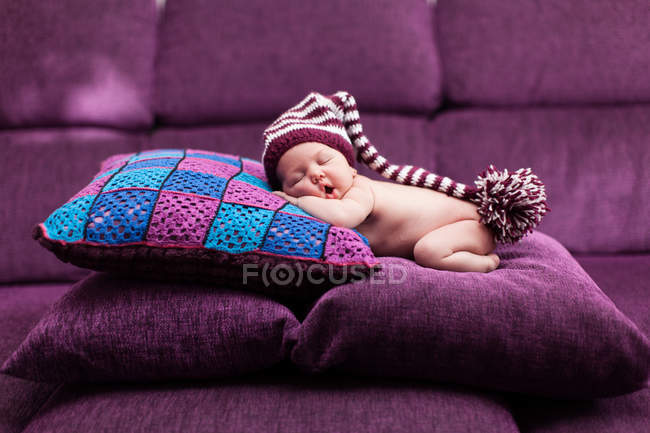 Sleeping baby girl wearing funny hat lying on stacked cushions — front view, lying down - Stock Photo | #194921946