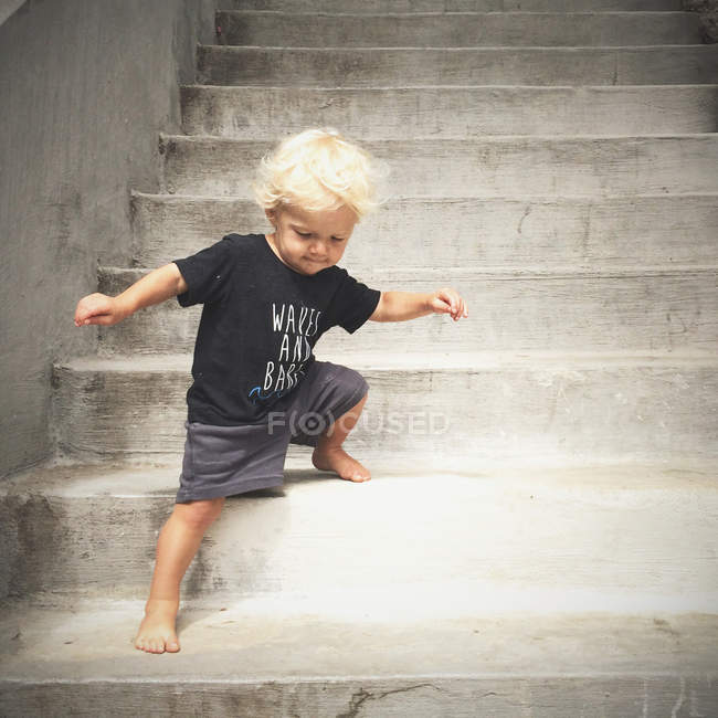 Baby boy going down on stairs — Stock Photo