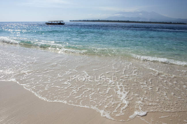 Indonesia, Blue ocean, white surf with boat on horizon — Stock Photo