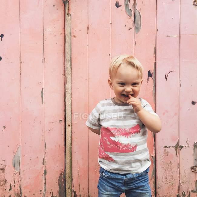 Smiling little boy standing outside pink garage door — Stock Photo