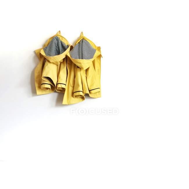 Two yellow raincoats hanging on white wall — Stock Photo