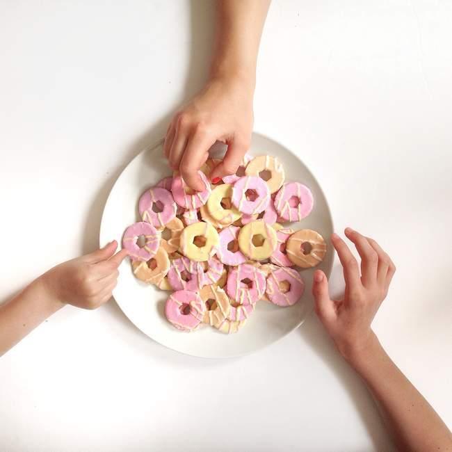Visão superior de mãos humanas tomando biscoitos da placa no fundo branco — Fotografia de Stock